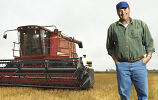 farmer standing in front of a harvester