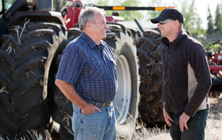 two men conversing in front of farm equipment